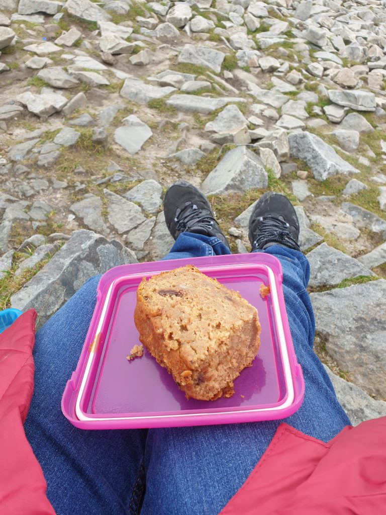 Eve Menezes Cunningham eating vegan choc chip banana cake at the top of the Reek (aka Croagh Patrick mountain), hugging the ground instead of admiring the view
