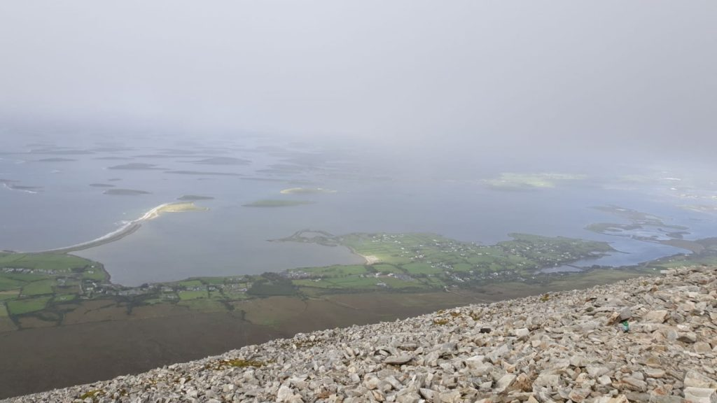 loose rock climb view of Clew Bay from the Reek (aka Croagh Patrick mountain) in Ireland